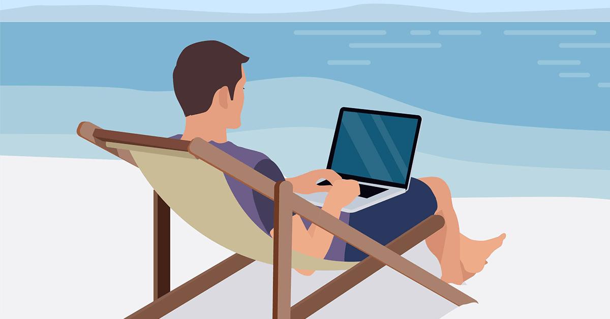 Guy on laptop sitting on the beach